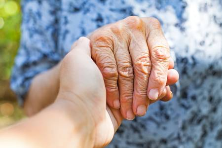 86165392-close-up-elderly-female-s-shaking-hand-held-by-young-carer-s-hands-outdoor